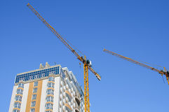 Completion of the apartment building. Light blue house, a yellow construction crane against the blue sky Royalty Free Stock Image