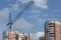 Completion of construction. Two apartment houses and the constru. Two completed monolith-brick house and a construction crane against the sky Stock Images