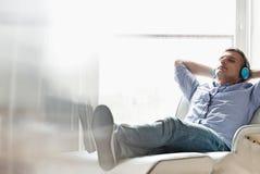 Completo do homem de meia idade relaxado que escuta a música em casa imagens de stock royalty free