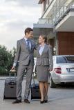 Completo dos pares do negócio que andam com bagagem fora do hotel Imagem de Stock Royalty Free