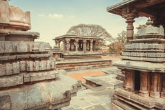 Complex of ancient buildings of Halebidu, with carved walls and columns of the 12th century Hoysaleshwara temple, India. Stock Images