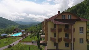 Complex of Apartments, Pool and Mountains. Drone shoots a panorama of tourist apartments, the pool and mountains. Green trees and grass stock video