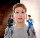 Complex feelings. Teenage boy in contradiction, on one shoulder  sits an angel, and on other sits devil Stock Photography