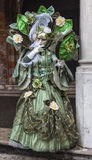 Complex Green Venetian Disguise. Venice, Italy-February 19, 2012: Image of a person disguised in a complex green costume during the Venice carnival days Stock Image