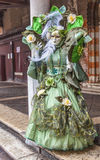 Complex Green Venetian Disguise. Venice, Italy-February 19, 2012: Image of a person disguised in a complex green costume during the Venice carnival days Stock Photos