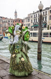 Complex Green Venetian Disguise. Venice, Italy-February 19, 2012: Image of a person disguised in a complex green costume near the Grand Canal during the Venice stock images