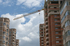 Complex of houses, the tower crane on the sky background. Complex of houses, a tower crane on a background of the cloudy sky Stock Images