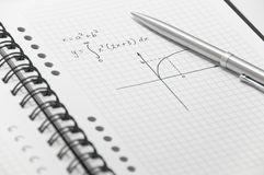Complex math formula (with simple graph). On white spiral notebook with elegant silver pen Stock Photos