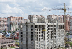 A complex of new buildings. Unfinished apartment house on a background of a complex of new buildings Stock Images