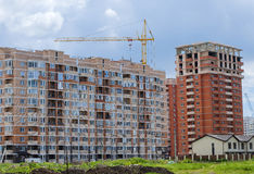 Complex of residential high-rise and single-storey houses. And tower crane on a background of the cloudy sky Royalty Free Stock Photos