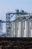 The complex silo installations for the storage of grain standing in the plowed Royalty Free Stock Photos
