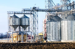 The complex silo installations for the storage of grain standing in the plowed Royalty Free Stock Photo