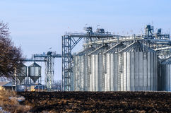 The complex silo installations for the storage of grain standing in the plowed Royalty Free Stock Images