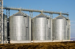 The complex silo installations for the storage of grain standing in the plowed Royalty Free Stock Image