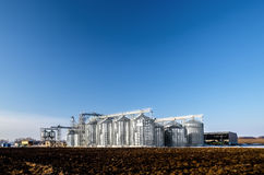 The complex silo installations for the storage of grain standing in the plowed Stock Photos