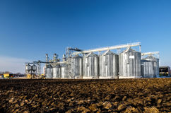The complex silo installations for the storage of grain standing in the plowed Stock Image