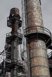 Complex of smokestacks with ladders and walkways, industrial steel manufacturing site. Vertical aspect royalty free stock image