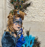 Complex Venetian Disguise. Venice,Italy- March 2, 2014: Environmental portrait of a woman wearing a complex blue disguise with peacock feathers,butterfly and Royalty Free Stock Images