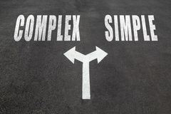 Complex vs simple choice concept. Two direction arrows on asphalt Stock Image