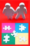 Complexity of relationships. Male and female wooden figures standing in front of puzzle pieces on coloured paper stock photography