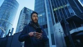 Complexo do negócio com um homem que opera seu smartphone ao lado dele filme