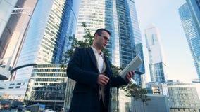 Complexo do negócio feito dos arranha-céus com um homem de negócios masculino bem sucedido novo que está perto dele vídeos de arquivo