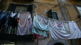 Complexo residencial dilapidado com as pilhas da secagem lavada da lavanderia em balcões filme
