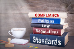 Compliance concept. Stack of books on wooden desk.  Royalty Free Stock Photography