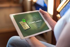 Compliance concept on a tablet. Woman holding a tablet showing compliance concept stock photos