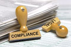 Compliance and legal printed on stamps. Laying on stack of forms royalty free stock photo