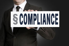 Compliance placard is held by businessman Royalty Free Stock Photography