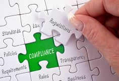 Compliance puzzle with female hand and text. Compliance business puzzle with female hand and text - regulations, policies, requirements, rules, standards royalty free stock photo