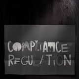 Compliance Regulation design words. On dark crumpled paper as concept Stock Image