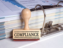 Compliance. Text 'compliance' in black uppercase letters inscribed on the wooden part of a rubber stamp leaning against a binder revealing a bar chart and stock photos