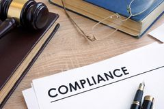 Compliance on a desk with books. Compliance on a wooden desk with books stock images