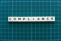 Compliance word made of square letter word on green background. stock photography