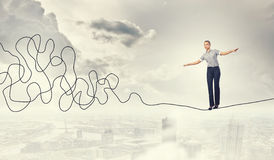 Complicated case. Young businesswoman walking on twisted rope high in sky Stock Image