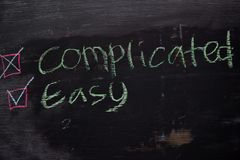 Complicated or Easy written with color chalk concept on the blackboard stock photos