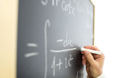 Complicated mathematical equation. Closeup of teacher writing complicated mathematical equation on black board royalty free stock photo