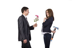 Complicated relationships. Young male gives flowers to beautiful female She pretends pleased and happy but keeps iron axe hidden behind her body Royalty Free Stock Images