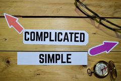 Complicated or Simple opposite direction signs with eyeglasse and compass on wooden. Vintage background. Business and education on inspiration concepts stock images