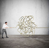 Complicated tangle. Businessman trying to solve the complicated tangle Stock Image