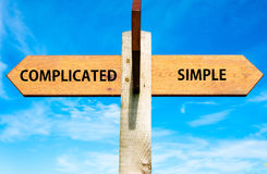 Complicated versus Simple. Wooden signpost with two opposite arrows over clear blue sky, Complicated versus Simple messages Royalty Free Stock Photography