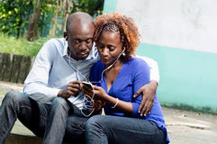 Complicity and commnication. This couple sitting in a park share a phone information through headphones stock images