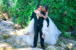 Complicity. Couple of bride and groom in nature, showing great joy and complicity royalty free stock image