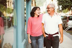 Complicity between father and daughter. Mature father and young daughter having fun walking on the street stock photography