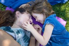 Complicity between mother and daughter. Woman mother and four years old blonde child laughing together, looking with complicity, lying on towels in the green royalty free stock images
