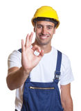 Compliment from a latin construction worker. Compliment from a laughing latin construction worker on an isolated white background for cut out royalty free stock photography