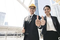 Compliment of teamwork, businesspeople show thumb to praise and. Great sign for parthner outside of building royalty free stock photo