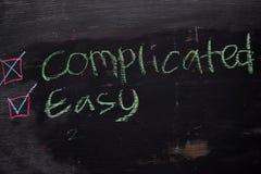 Compliqué ou facile écrit avec le concept de craie de couleur sur le tableau noir photos stock